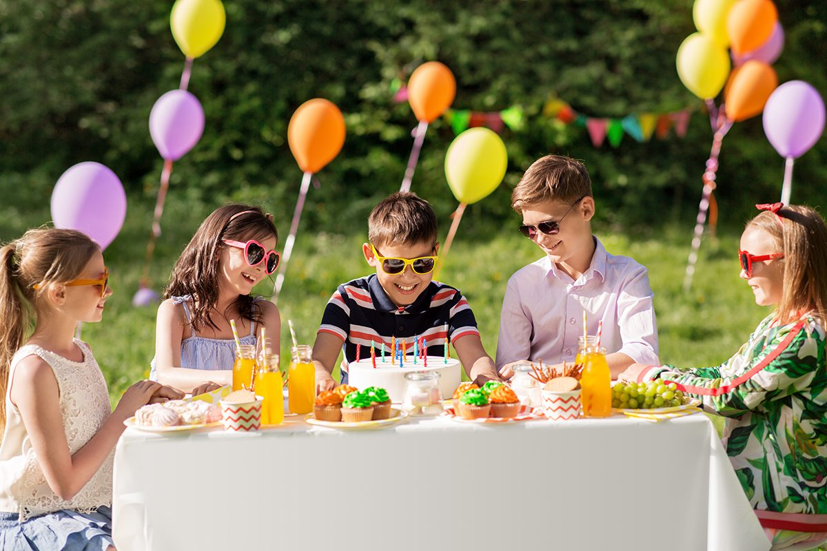 holidays, childhood and celebration concept - happy kids with candles on birthday cake sitting at table at summer garden party